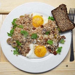 Kepti kiaušiniai su grikiais, saulėje džiovintais pomidorais ir alyvuogėmis